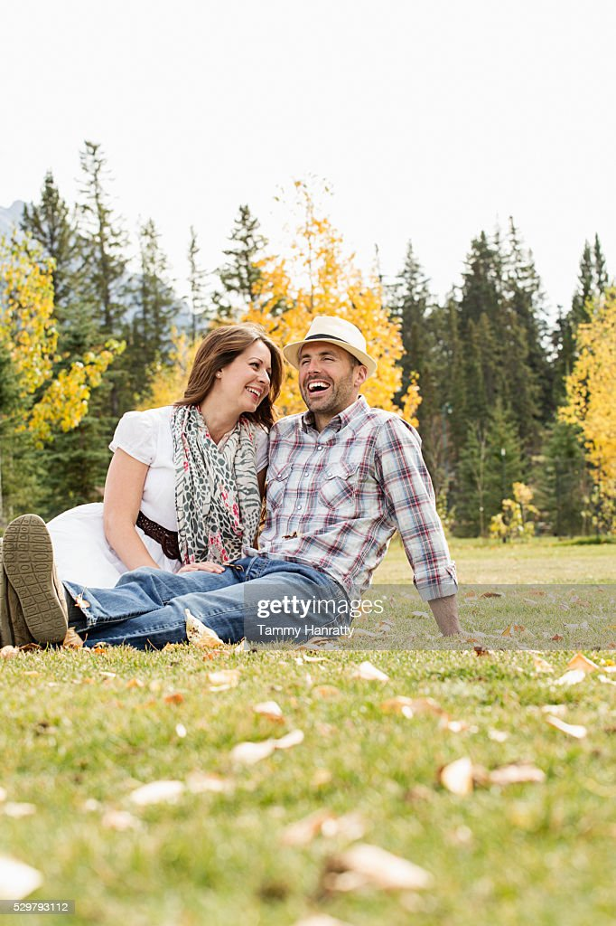 Mid-adult couple relaxing on grass : Stock Photo