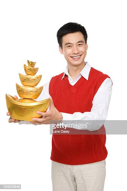 Mid-adult man holding decorative gold ingots
