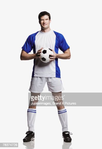 Mid-adult man holding soccer ball