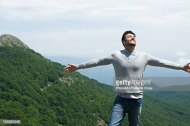 Mid-adult man with eyes closed and arms outstretched, mountainscape in background