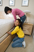 Mid-adult woman and her daughter making a bed