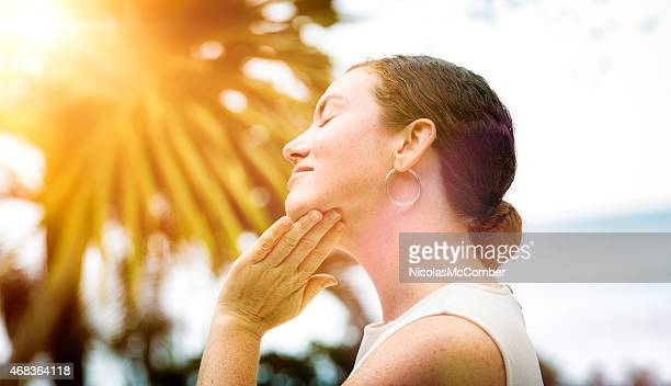 Mid-adult woman applies lotion to her face outdoors profile