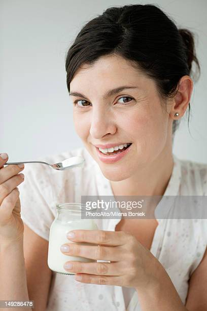 Mid-adult woman eating yogurt, portrait