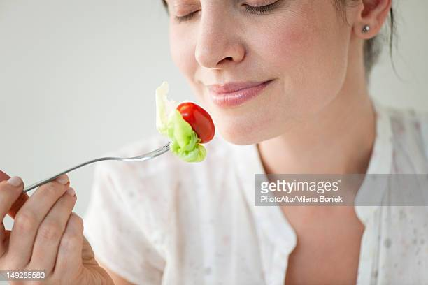 Mid-adult woman enjoying fresh vegetables