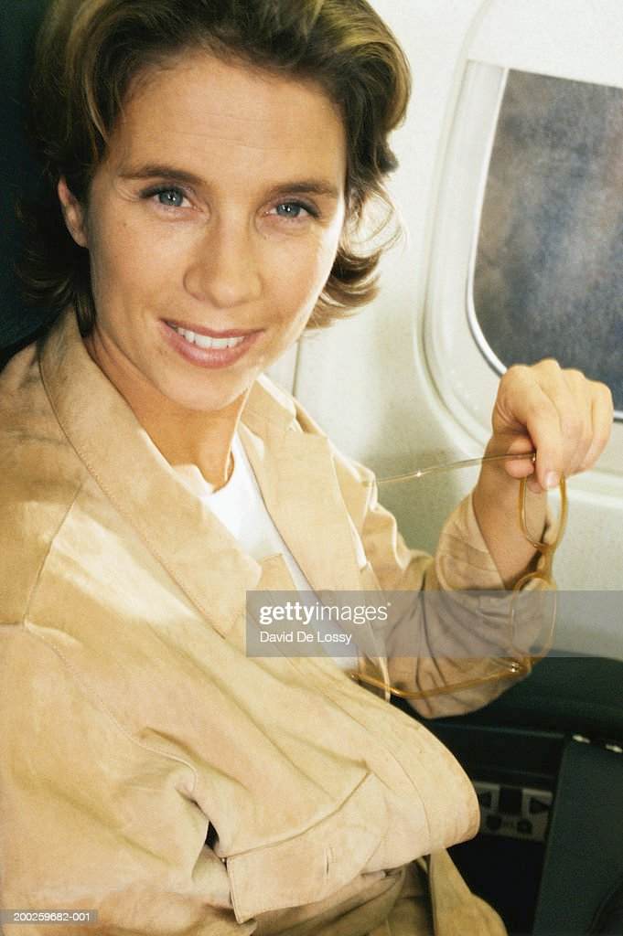 Mid-adult woman in airplane, portrait