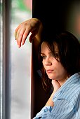 Midadult woman in man's shirt leans on window frame