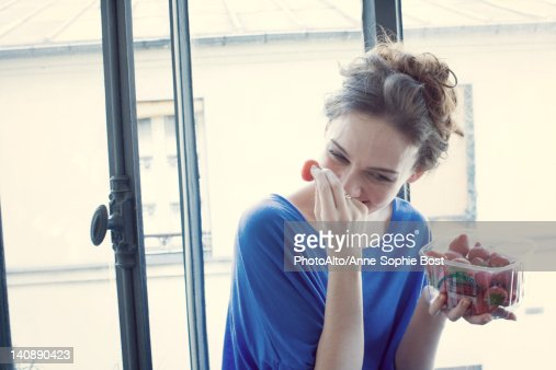 Mid-adult woman laughing while eating strawberries