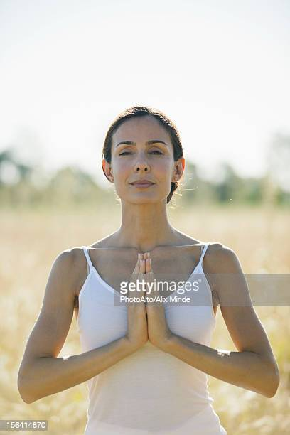 Mid-adult woman meditating outdoors
