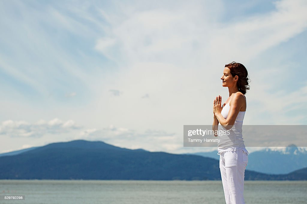 Mid-adult woman meditating while practicing yoga at sea : Stock Photo