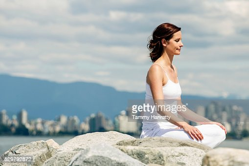 Mid-adult woman meditating while practicing yoga at sea : Bildbanksbilder