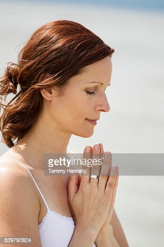 Mid-adult woman meditating while practicing yoga : Stockfoto