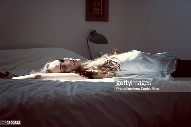 Mid-adult woman napping on bed