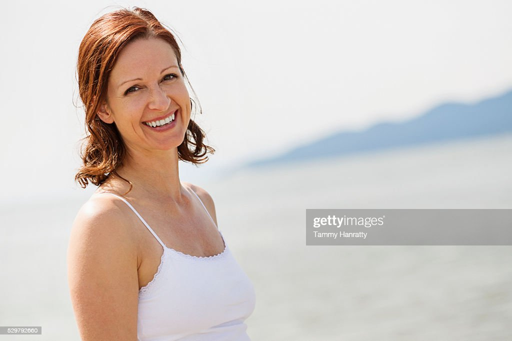 Mid-adult woman relaxing at sea looking at camera : Stock Photo