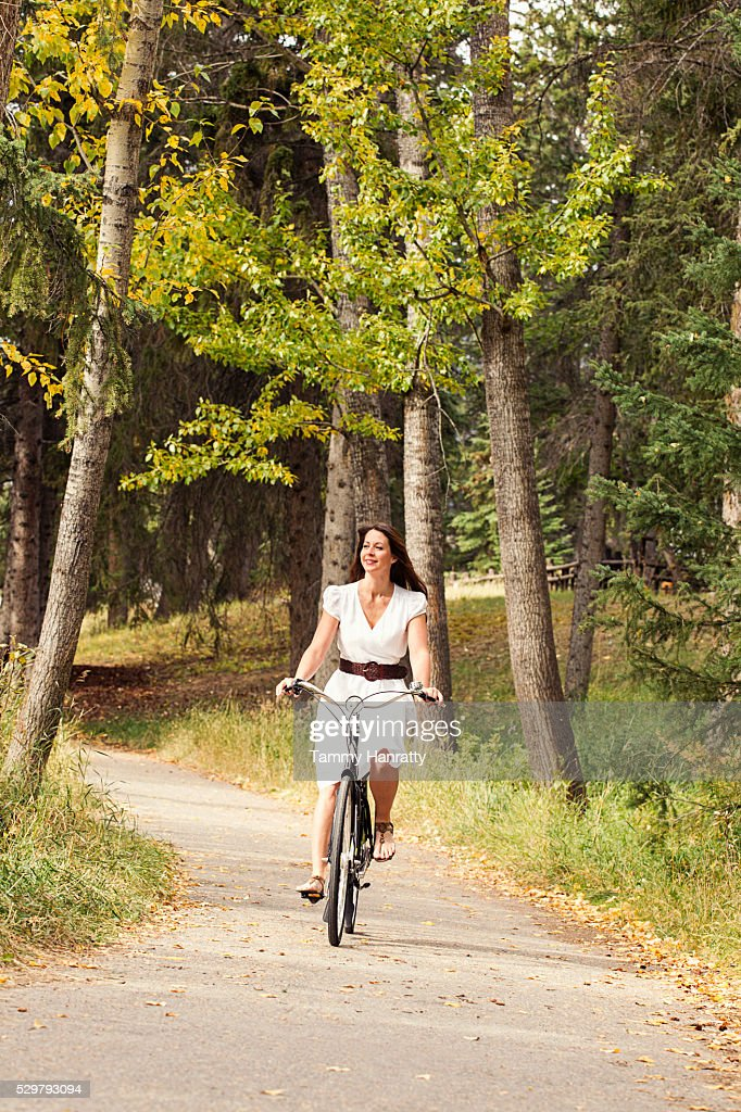 Mid-adult woman riding bike in forest : Stockfoto