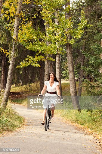 Mid-adult woman riding bike in forest : Stock-Foto