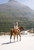Mid-adult woman riding horse on beach