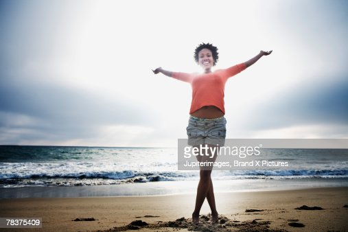 Mid-adult woman standing on beach with arms outstretched : ストックフォト