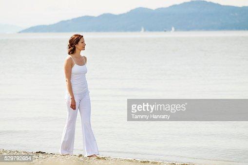 Mid-adult woman walking on beach : Stock Photo