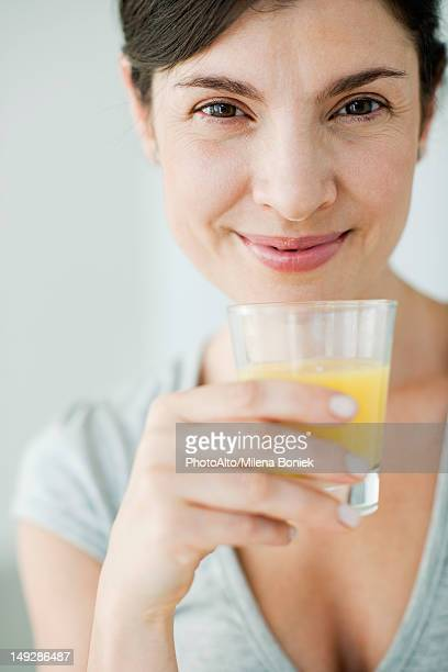 Mid-adult woman with glass of orange juice