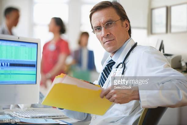 Meia-idade médico, olhando para a Câmera segurando uma pasta