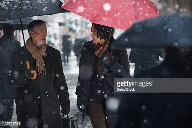 Mid-age man and Young woman talking while walking in the snow