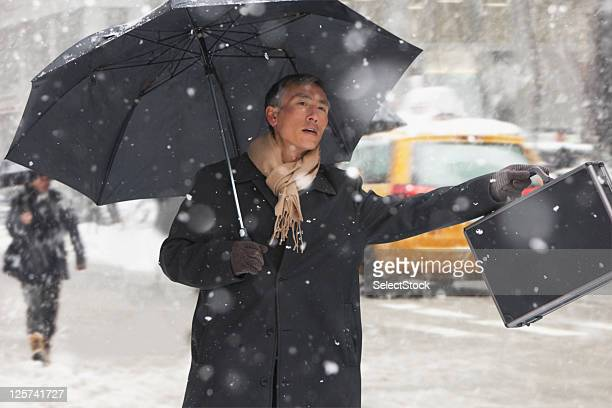 Mid-age man Hailing a cab in the snow