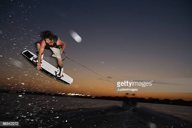 Midair wakeboarder at sunset