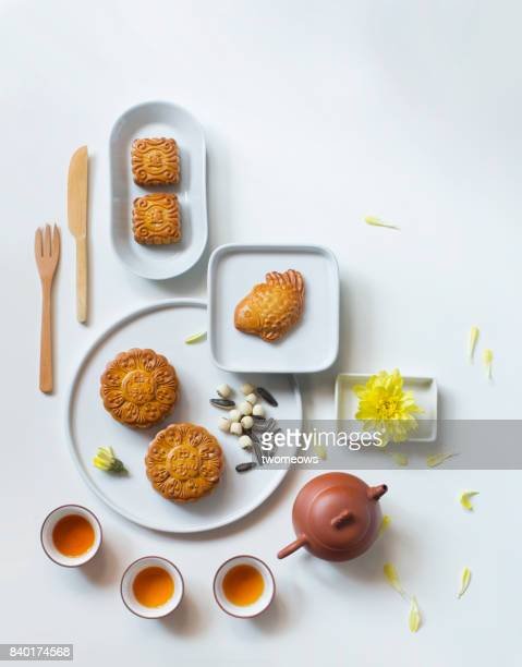 Mid-autumn festival tea party food and drink on white table top shot. Modern minimalist stylised image.