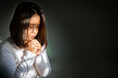 Middle adult Asian woman sitting and praying for blessings. According to religious beliefs. With light effect and dark vignette.