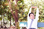Middle adult businessman sitting and relaxing in park. Stretching arms on top, smiling face, feeling happiness. Smart and charming businessman. Copy space with color filter and light effect.