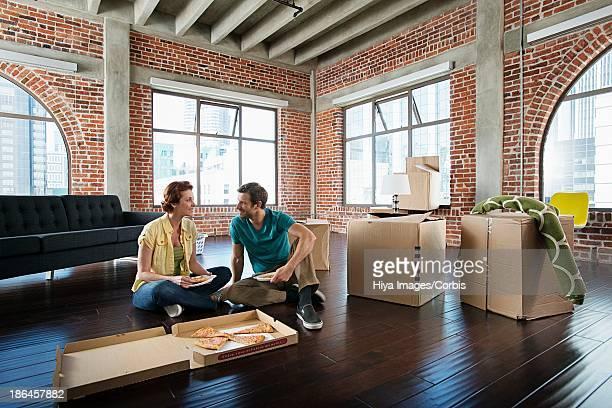 Middle adult heterosexual couple eating pizza on floor in empty living room