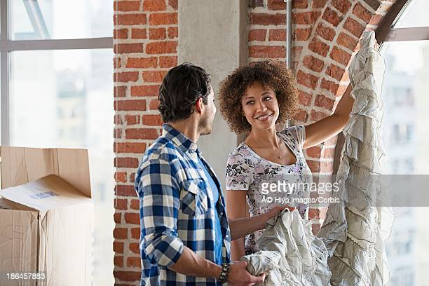 Middle adult heterosexual couple hanging curtains in empty living room