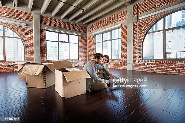 Middle adult heterosexual couple sitting in empty living room