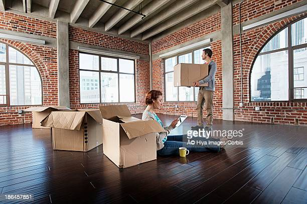 Middle adult heterosexual couple sitting in empty living room, Using mobile phone, Man holding cardboard box