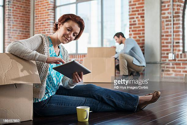 Middle adult heterosexual couple sitting in empty living room, Using mobile phone and packing cardboard box