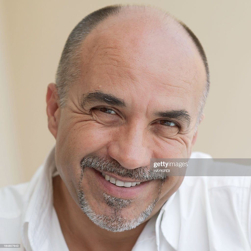 Middle age bald man smiling.