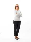 Full length portrait of casual businesswoman standing against white background while looking at camera and smiling.