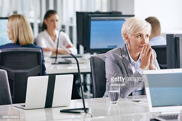 Middle age woman at work. Waiting for decisions. Doubts