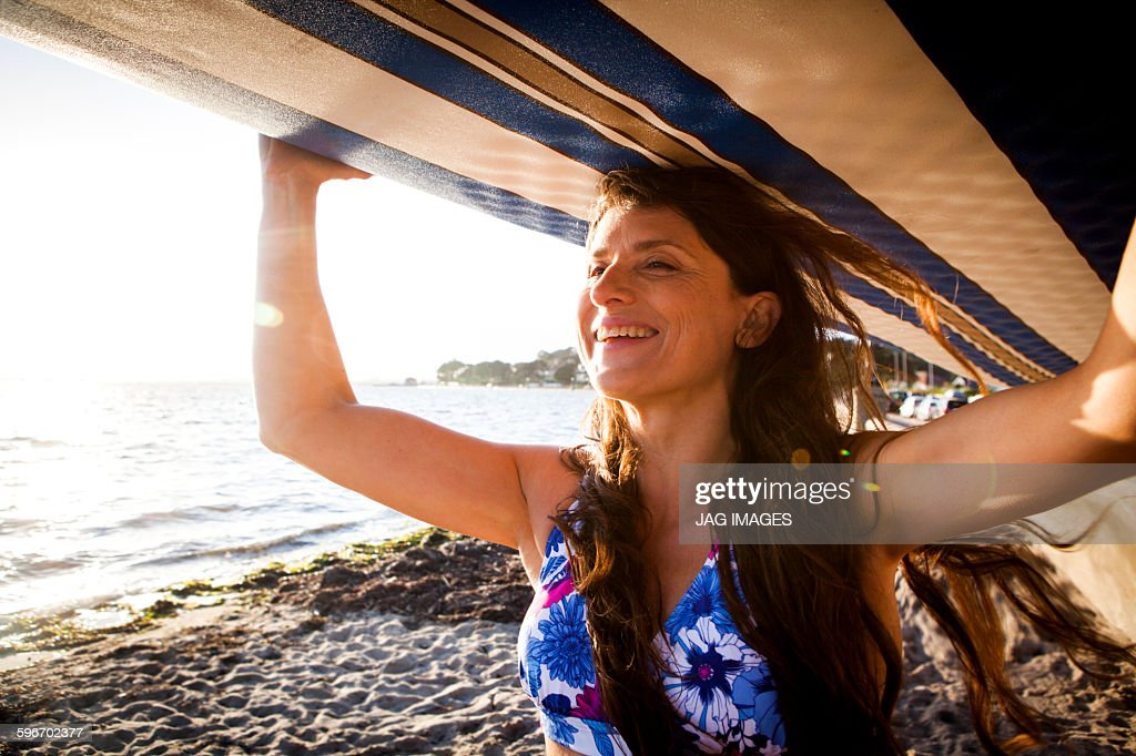 middle age woman prepares to go paddle boarding : Stock Photo