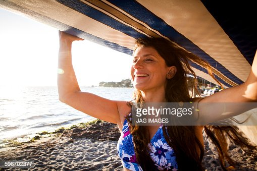 middle age woman prepares to go paddle boarding