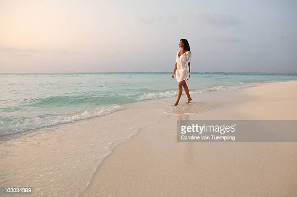 Middle age woman walking in shallows at beach