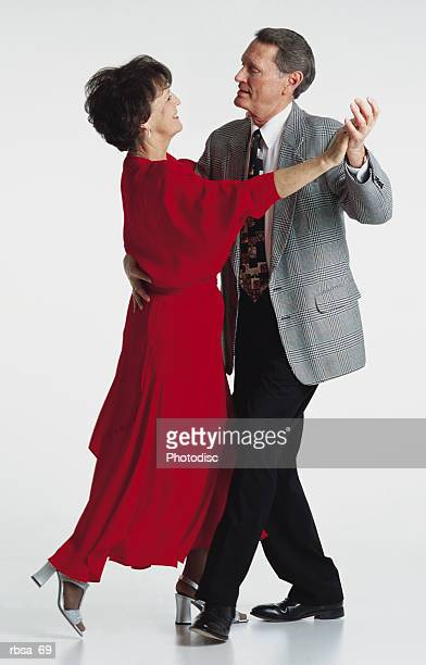 middle aged adult caucasian brunette female wearing a long red dress and middle aged adult caucasian gray haired male wearing a suit and tie holding each other in a dance pose as they look into each others eyes smiling