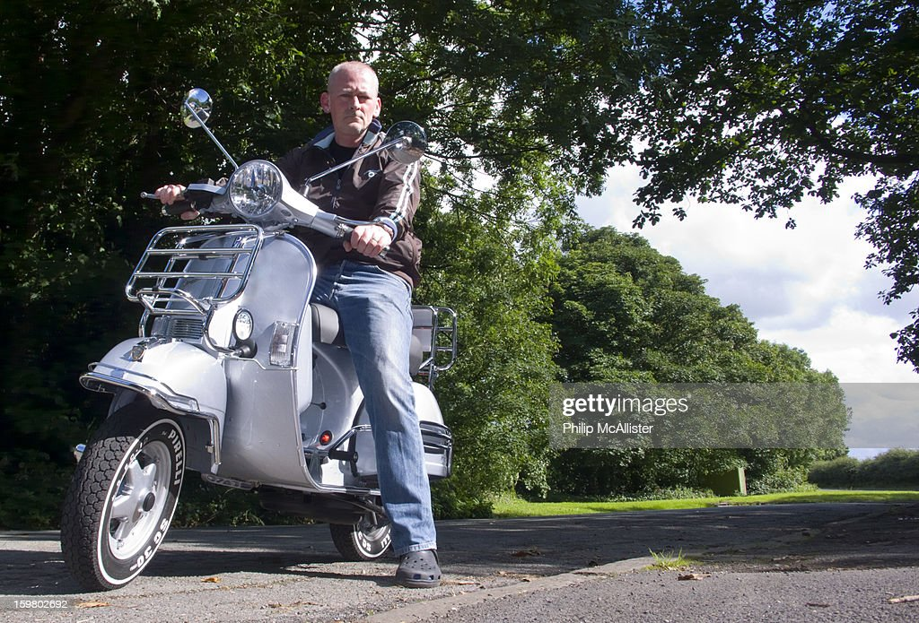 CONTENT] A middle aged balding man straddles a Vespa PX125.He is looking directly into the camera which is at a low viewpoint.