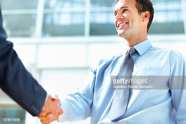 Middle aged business man shaking hands with executive