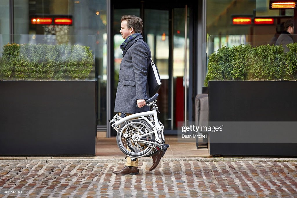 Middle aged businessman carrying his folding bicycle