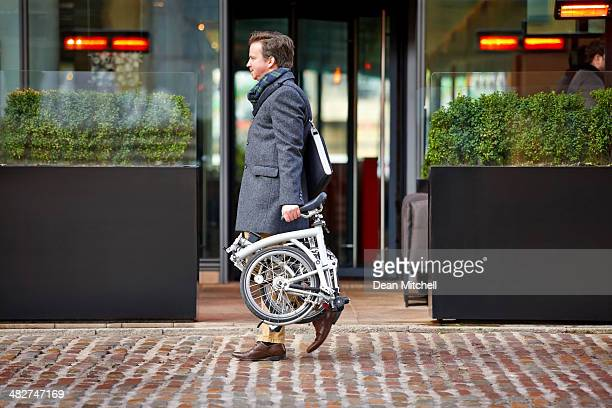 Mittleren Alter Geschäftsmann, tragen seine Falten Fahrrad