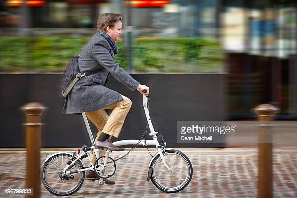 Middle aged businessman going to office by cycle