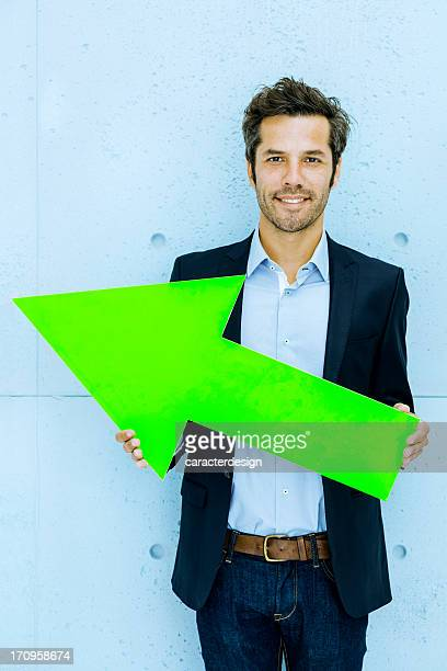 Middle aged businessman pointing left with green arrow