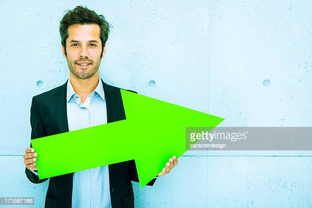 Middle aged businessman pointing right with green arrow