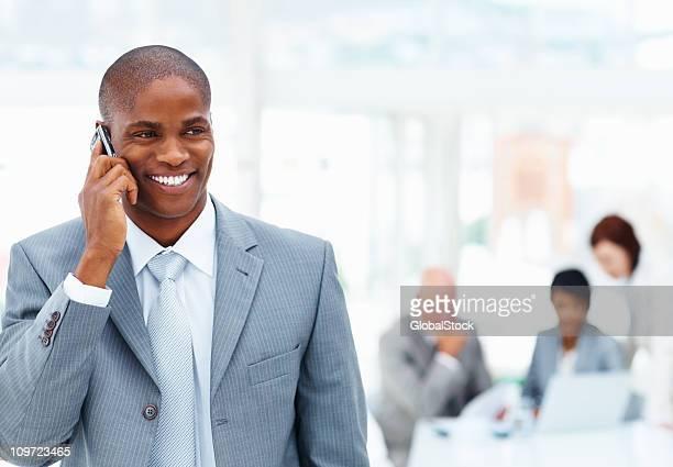 Mittleren Alter Geschäftsmann reden über cellphone und team in blur